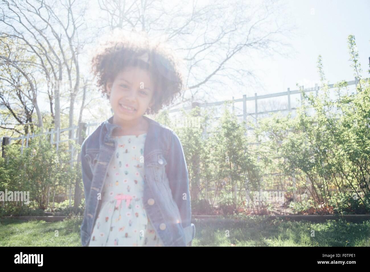Vorderansicht des Mädchens im Sonnenlicht, Hände hinter Rücken, Blick auf die Kamera zu Lächeln Stockbild