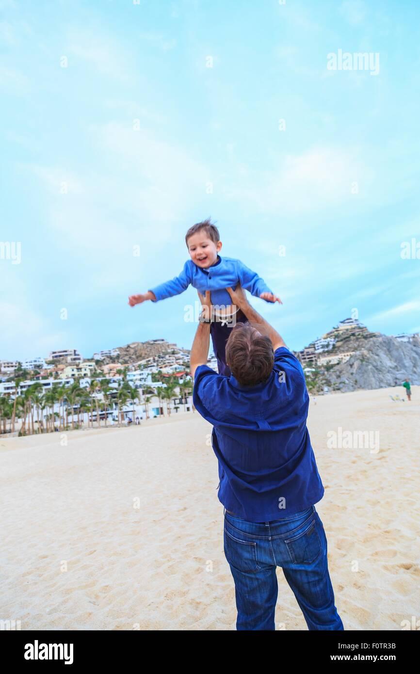 Anhebende Sohn Vater, am Strand, Rückansicht Stockbild