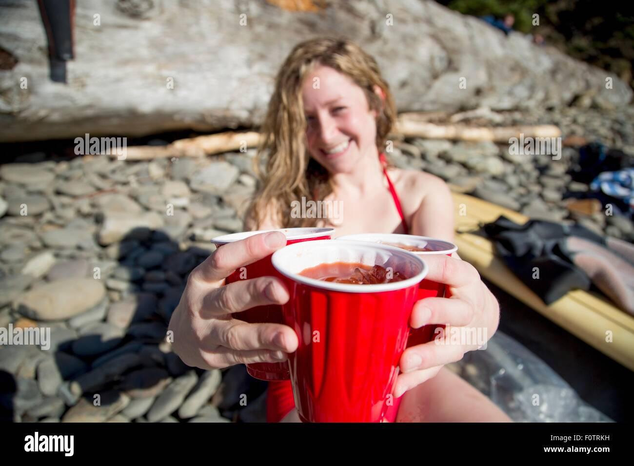 Junge Frau sitzt am felsigen Strand, hält Getränke, lächelnd, Short Sands Beach, Oregon, USA Stockbild