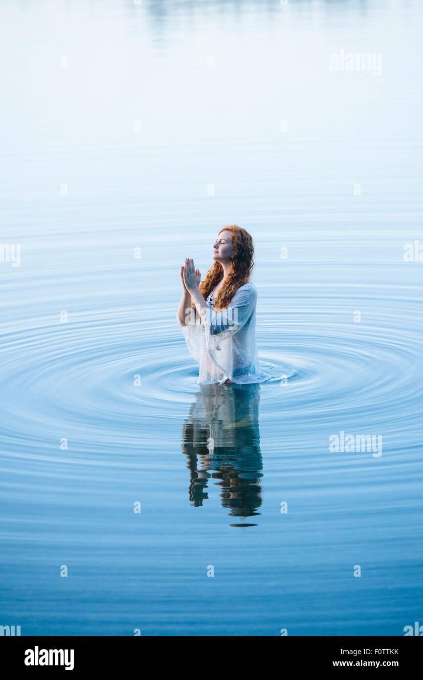 Junge Frau im See kräuselt sich mit geschlossenen Augen und Hände zusammen Stockbild