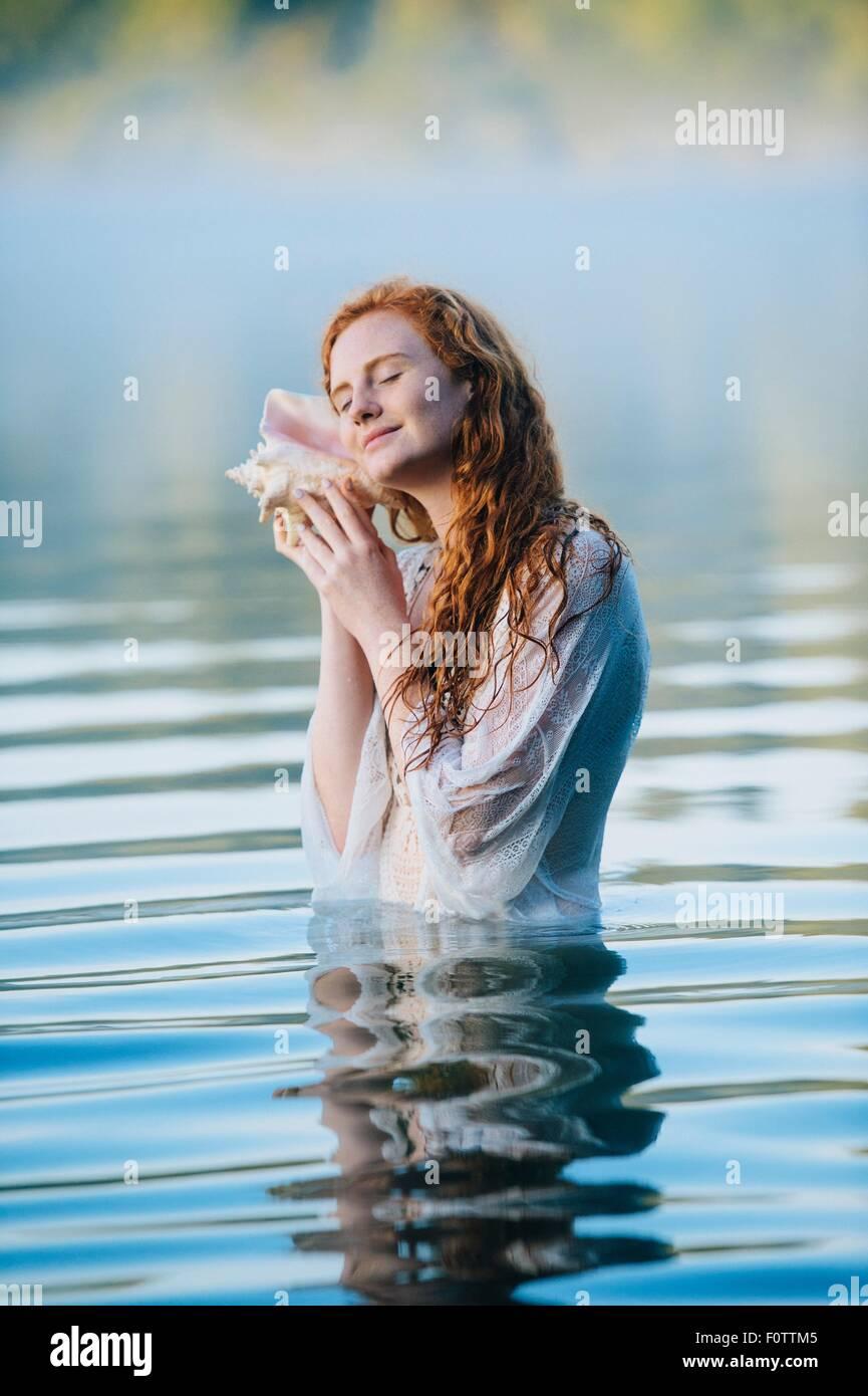 Junge Frau im nebligen See mit Augen geschlossen Muschel anhören Stockbild