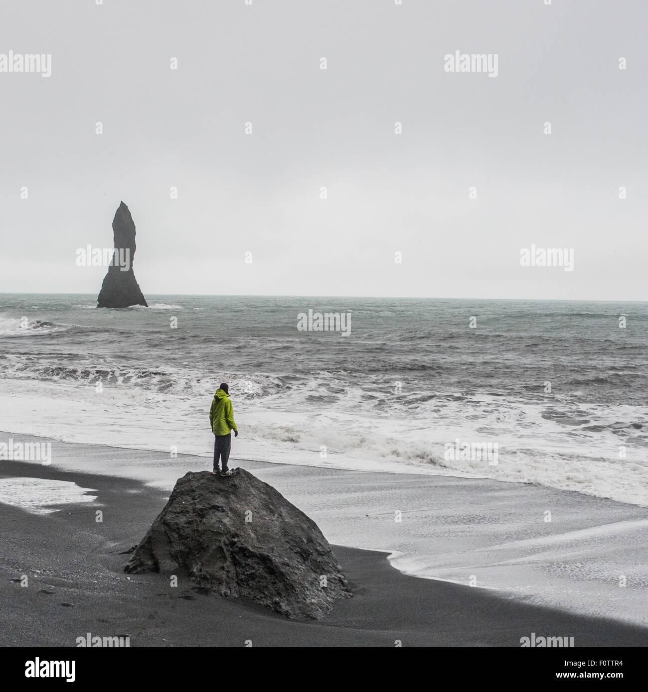 Junge männliche Touristen Blick auf das Meer von Felsformation, Reynisfjara, Island Stockbild
