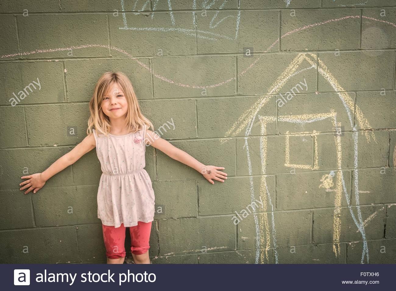 Mädchen vor Wand mit Kreidezeichnungen, Porträt Stockbild