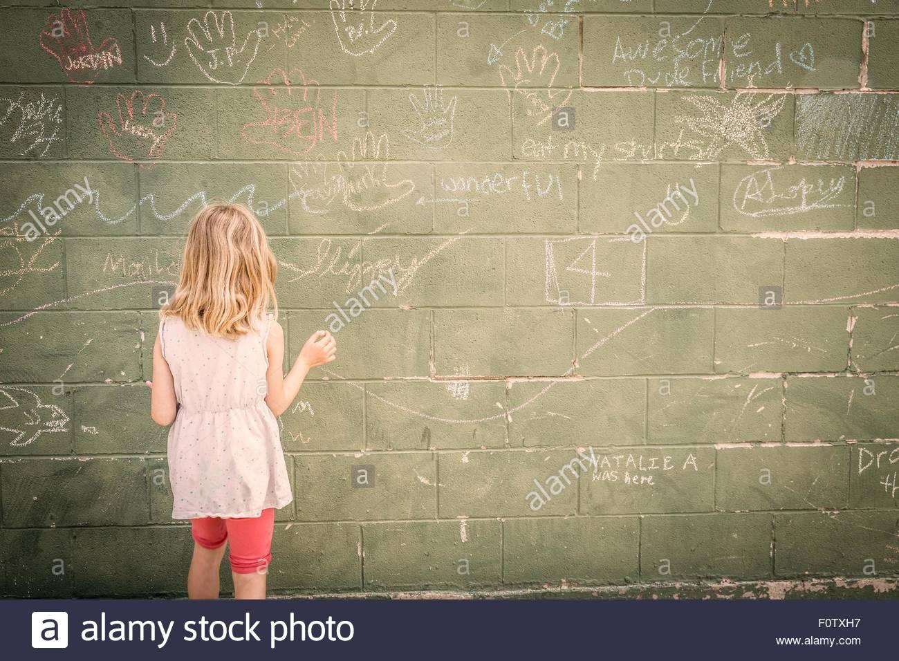 Mädchen vor Wand mit Kreidezeichnungen, Rückansicht Stockbild