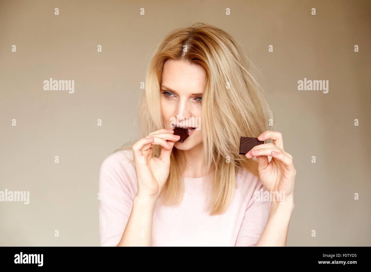 Portrait der schönen Frau mit langen blonden Haaren Essen Schokoriegel Stockbild