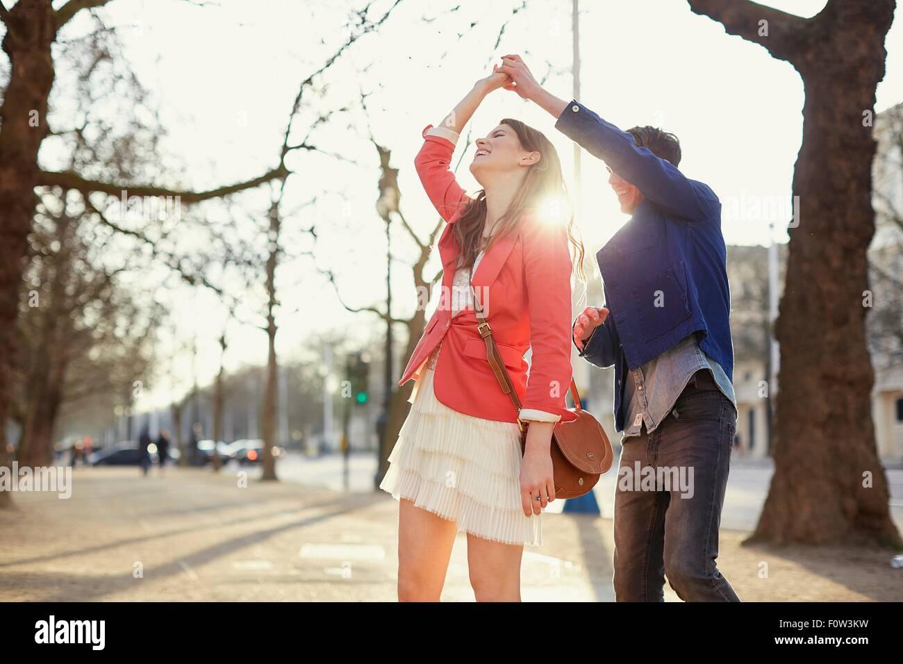 Romantisches Paar wirbelnd im sonnigen Park, London, UK Stockbild