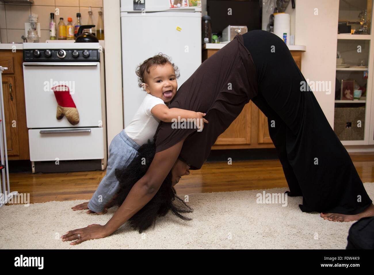 Mitte Erwachsene Frau Ausübung auf Teppich mit Kleinkind Tochter Stockbild