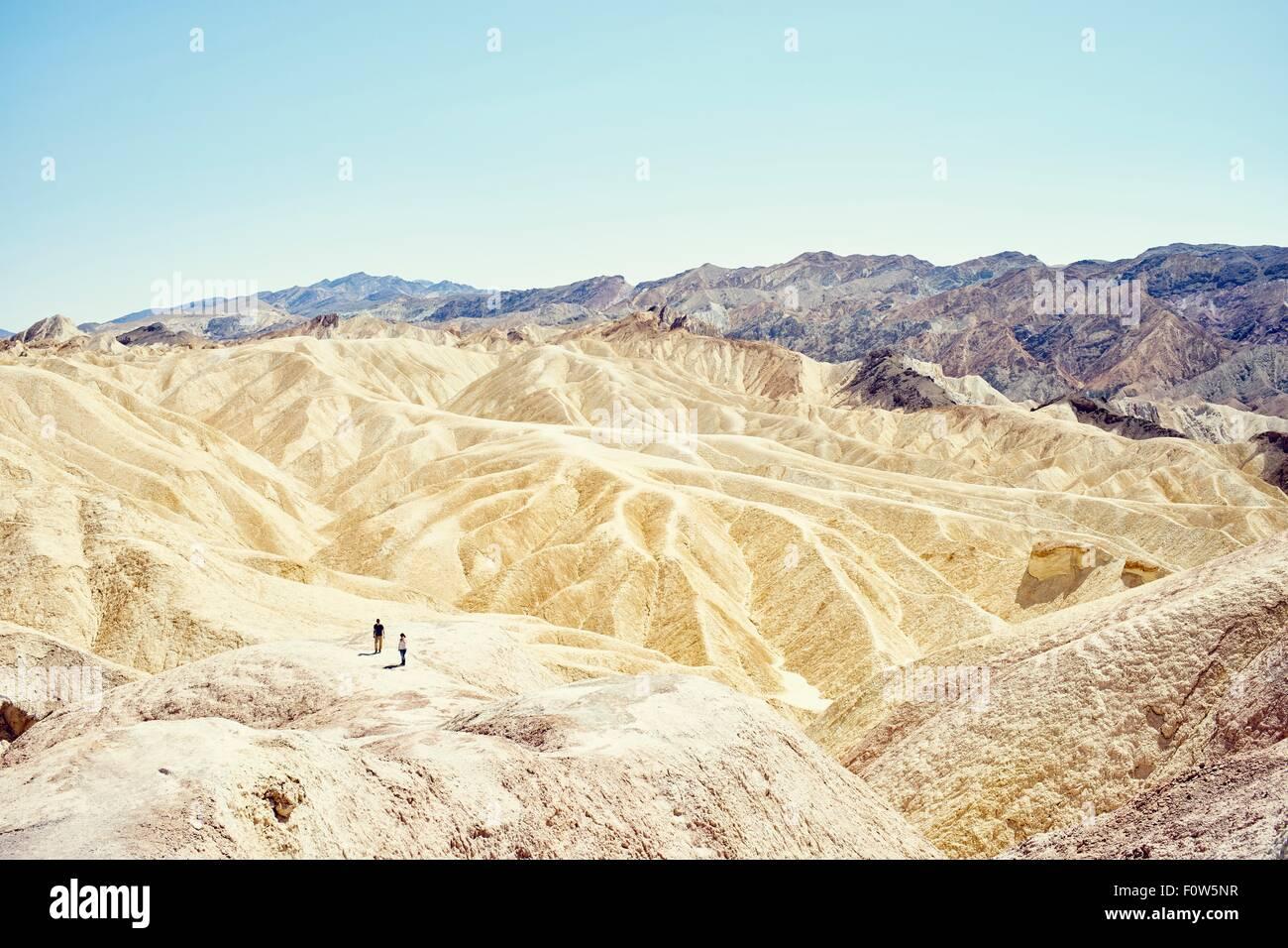 Blick auf zwei Touristen am Zabriskie Point, Death Valley, Kalifornien, USA Stockbild