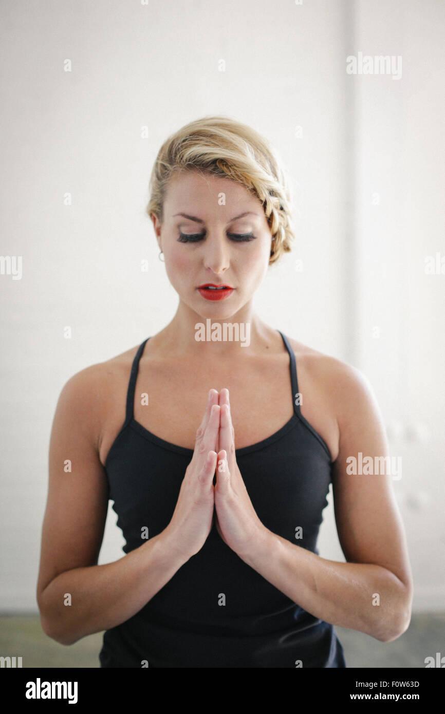 Eine blonde Frau in eine schwarze Trikot beim Yoga, stehen mit geschlossenen Augen und ihre Hände zusammen. Stockbild