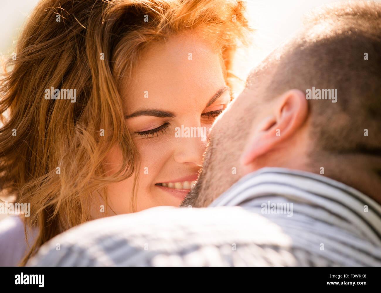 Candid Nahaufnahme Foto des Mannes küssen junge lächelnde Frau Stockbild