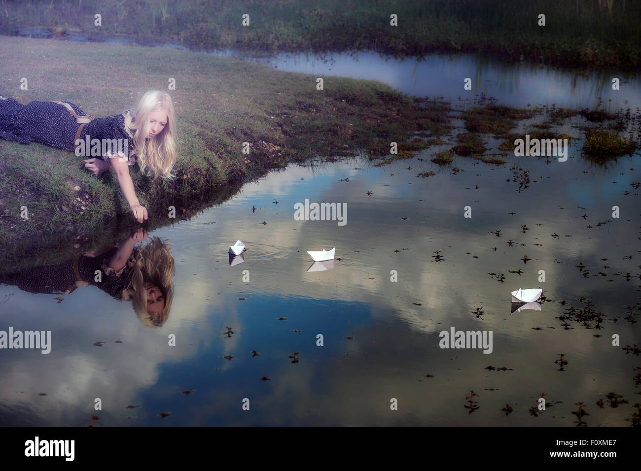 ein Mädchen mit drei Papierschiffchen in einem Teich Stockbild