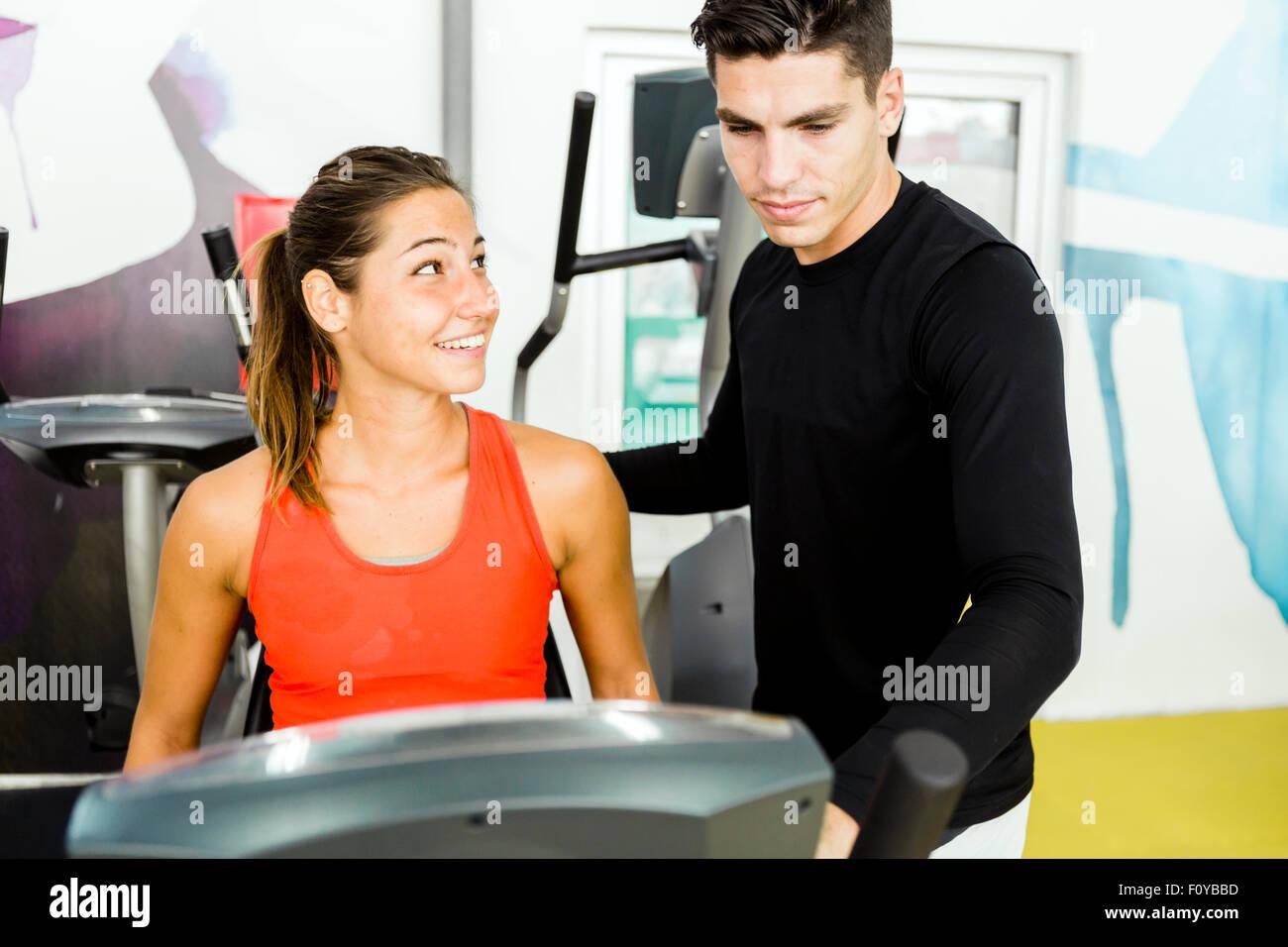 Schöne junge Frau beauftragt durch ein gut aussehender Mann in einer Turnhalle beim Radfahren Stockbild