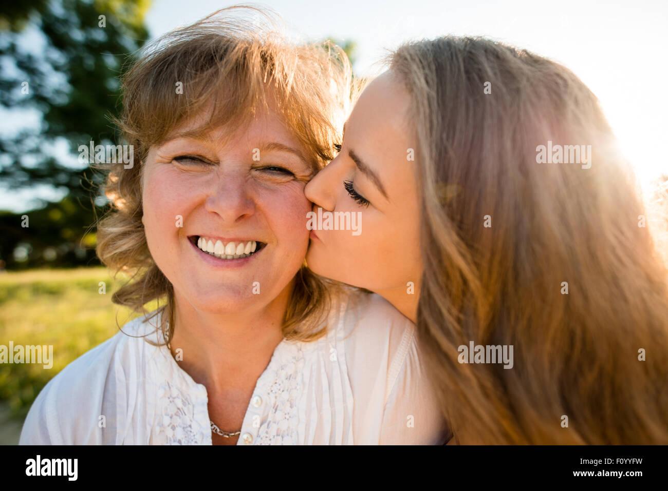 Teenager-Tochter küssen ihre Mutter im Freien in der Natur mit Sonne im Hintergrund, Weitwinkel Stockbild