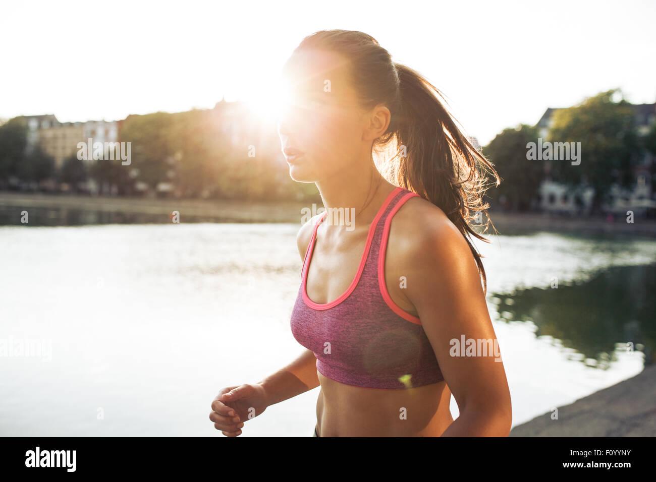 Im Freien Schuss von entschlossenen jungen Frau, für einen Lauf im Stadtpark. Sportlerin Joggen an einem Sommertag Stockbild