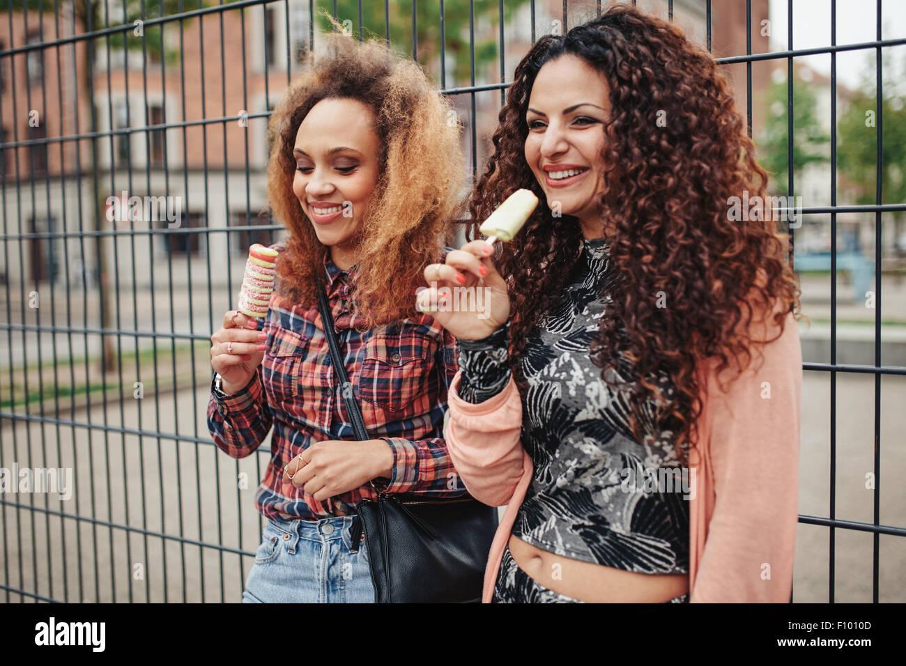 Fröhliche junge Mädchen essen Süßigkeiten Eis. Zwei junge Frauen stehen gegen einen Zaun lächelnd, Stockbild