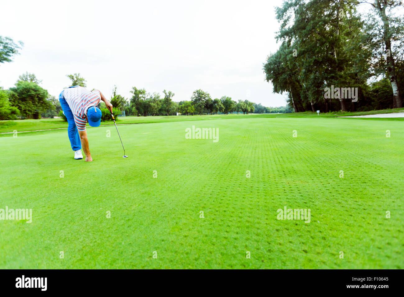 Golfer, die Kugel aus dem Loch auf einem schönen Kurs abrufen Stockbild