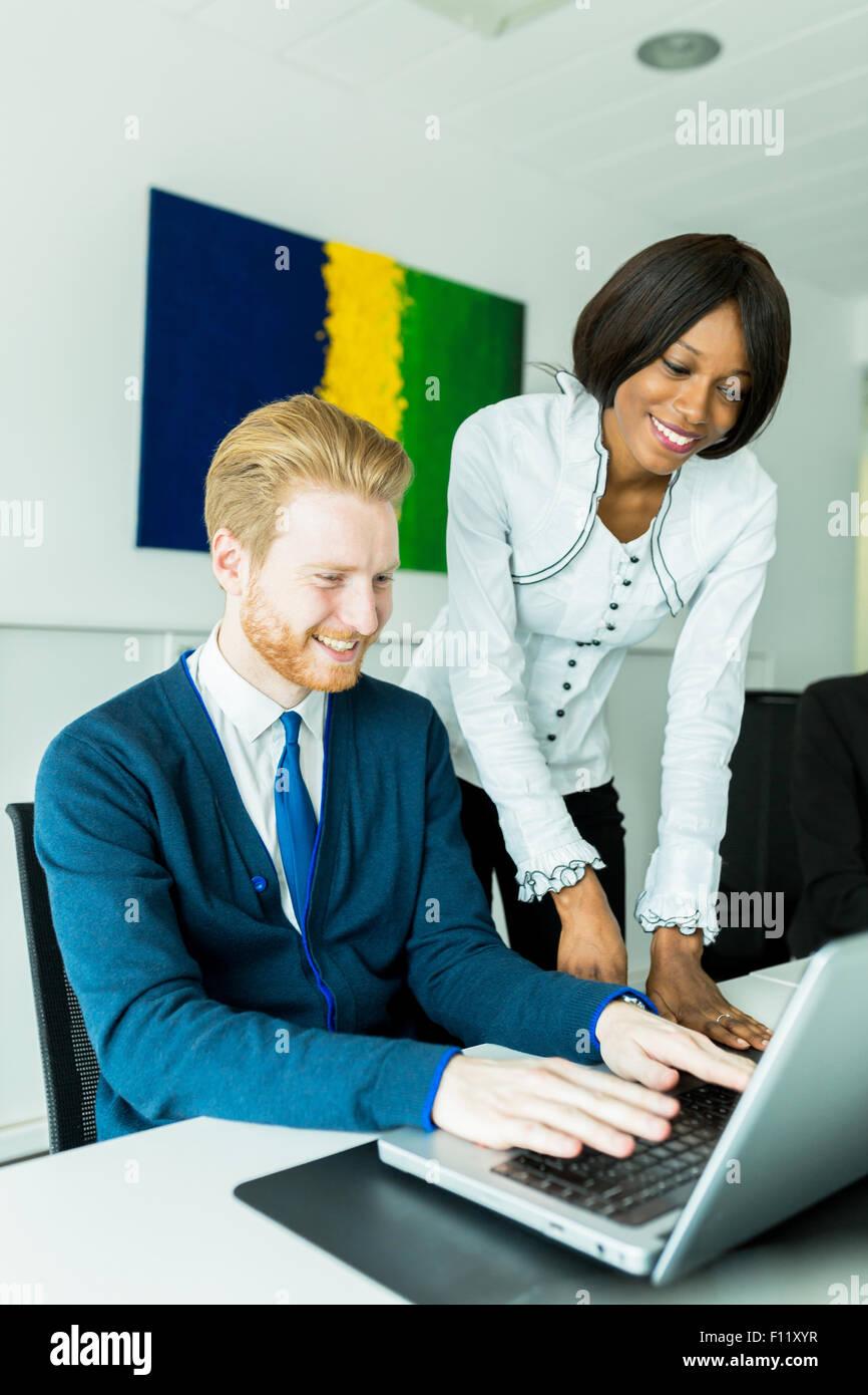 Geschäftsleute sprechen und Lächeln in einem Büro vor einem notebook Stockbild