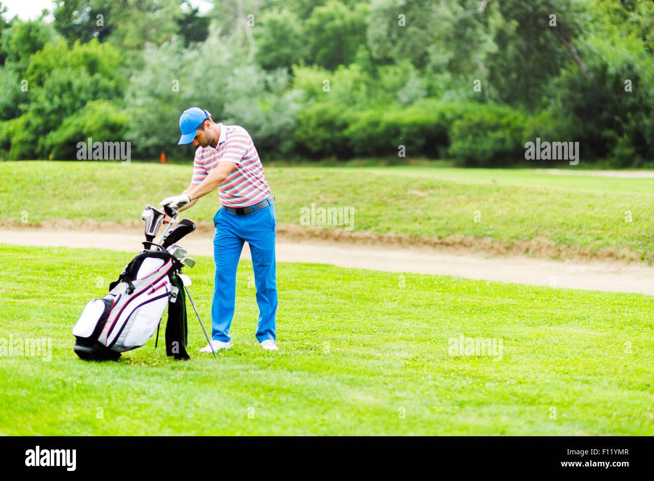 Golfer die Auswahl geeigneter Club für den nächsten Schuss Stockbild