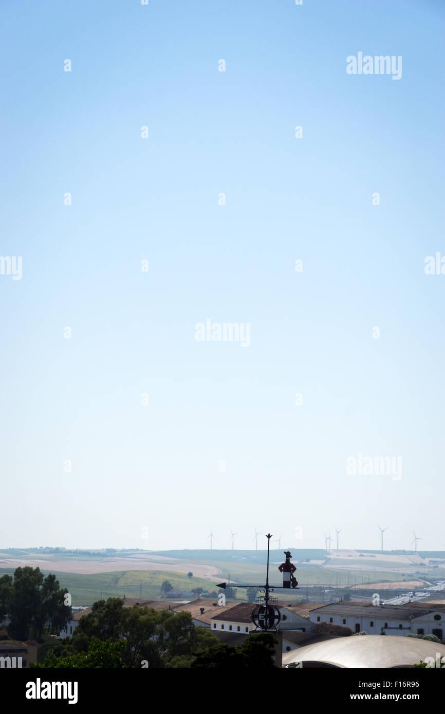 Windkraftanlagen am fernen Horizont von Jerez De La Frontera, Spanien, mit Tio Pepe gebrandmarkt Windfahne. Stockbild