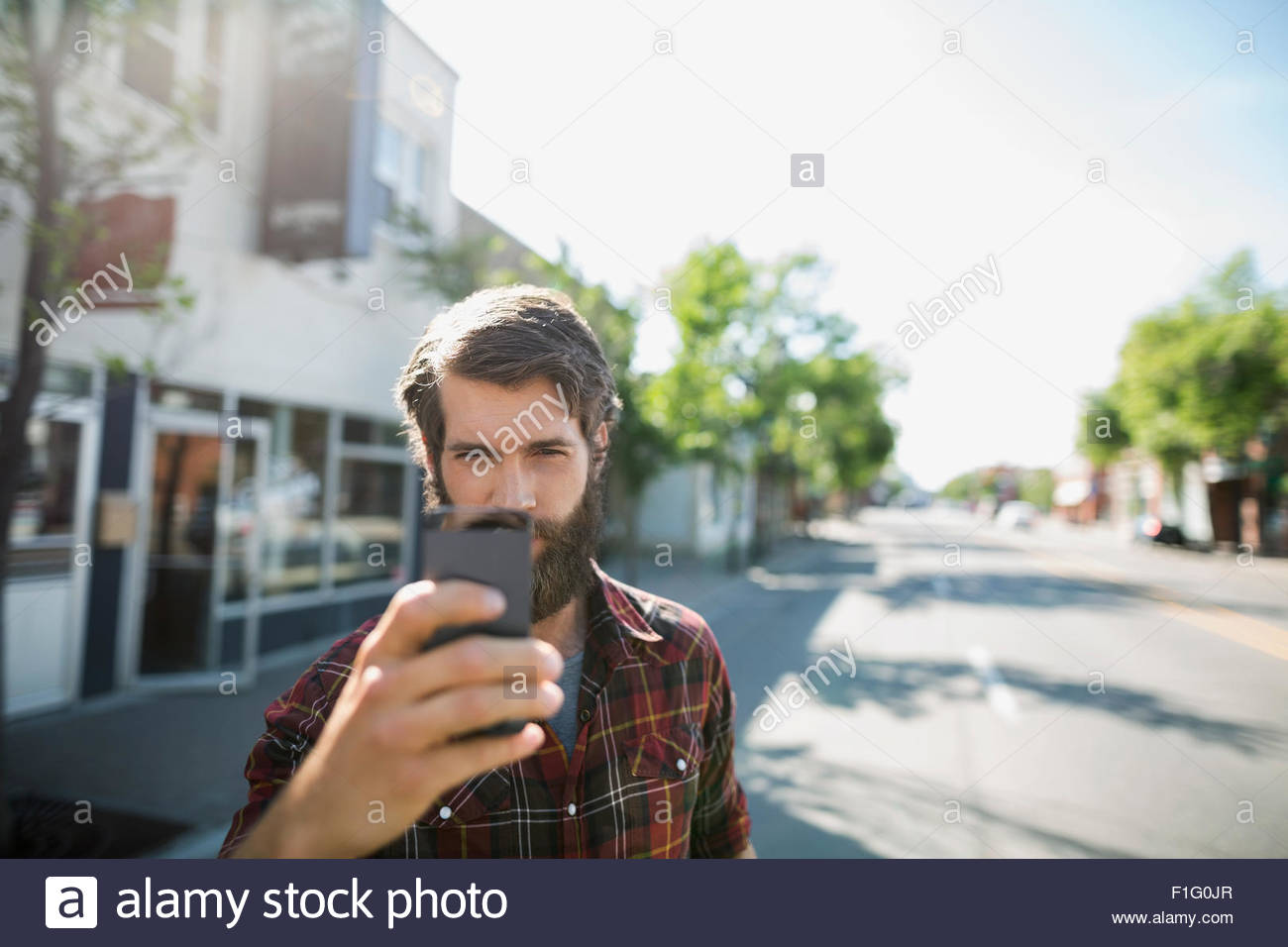 Bärtiger Mann Fotografieren mit der Kamera Telefon sonnige Straße Stockbild