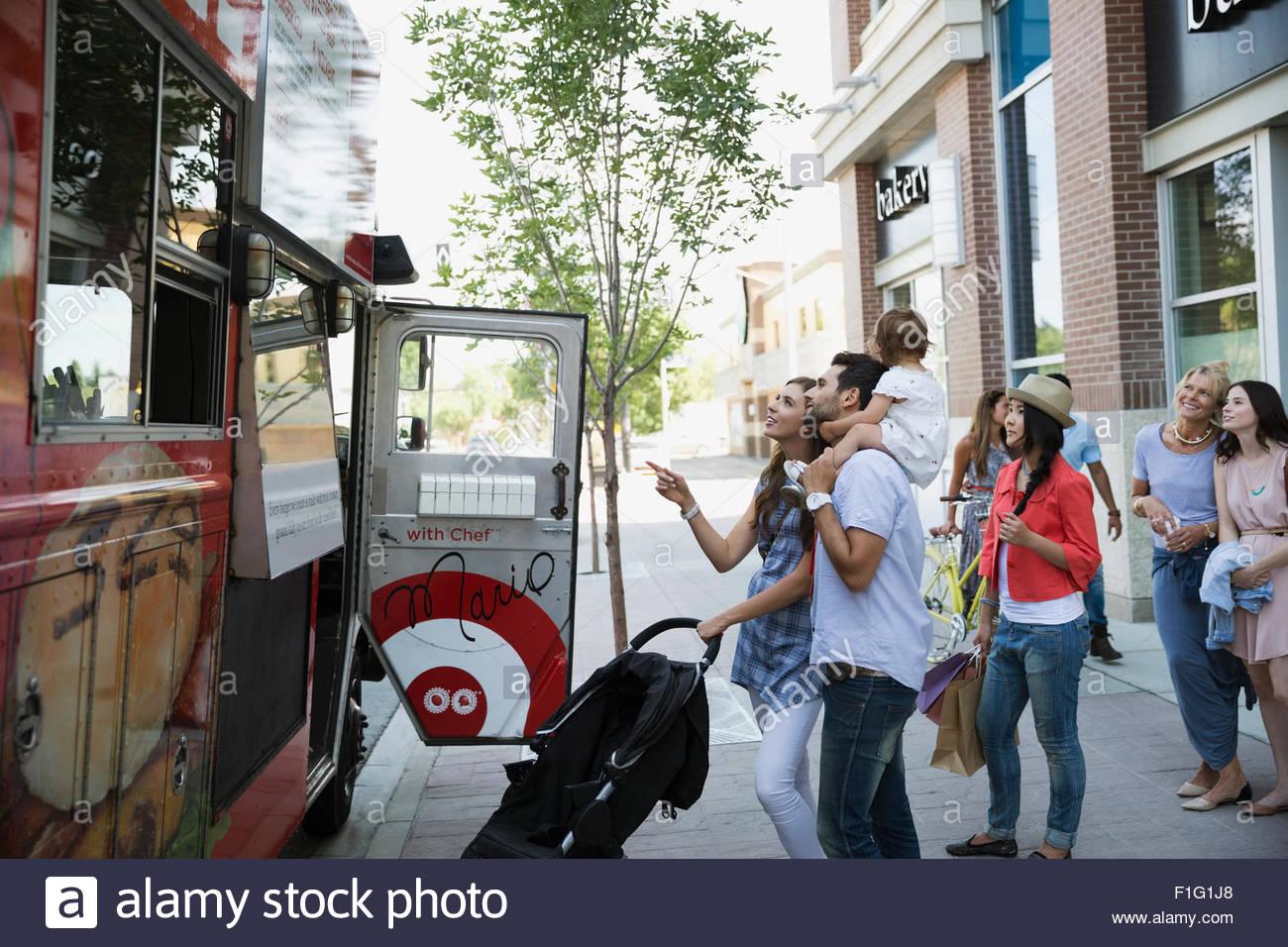 Kunden außerhalb Imbisswagen auf Bürgersteig Stockfoto