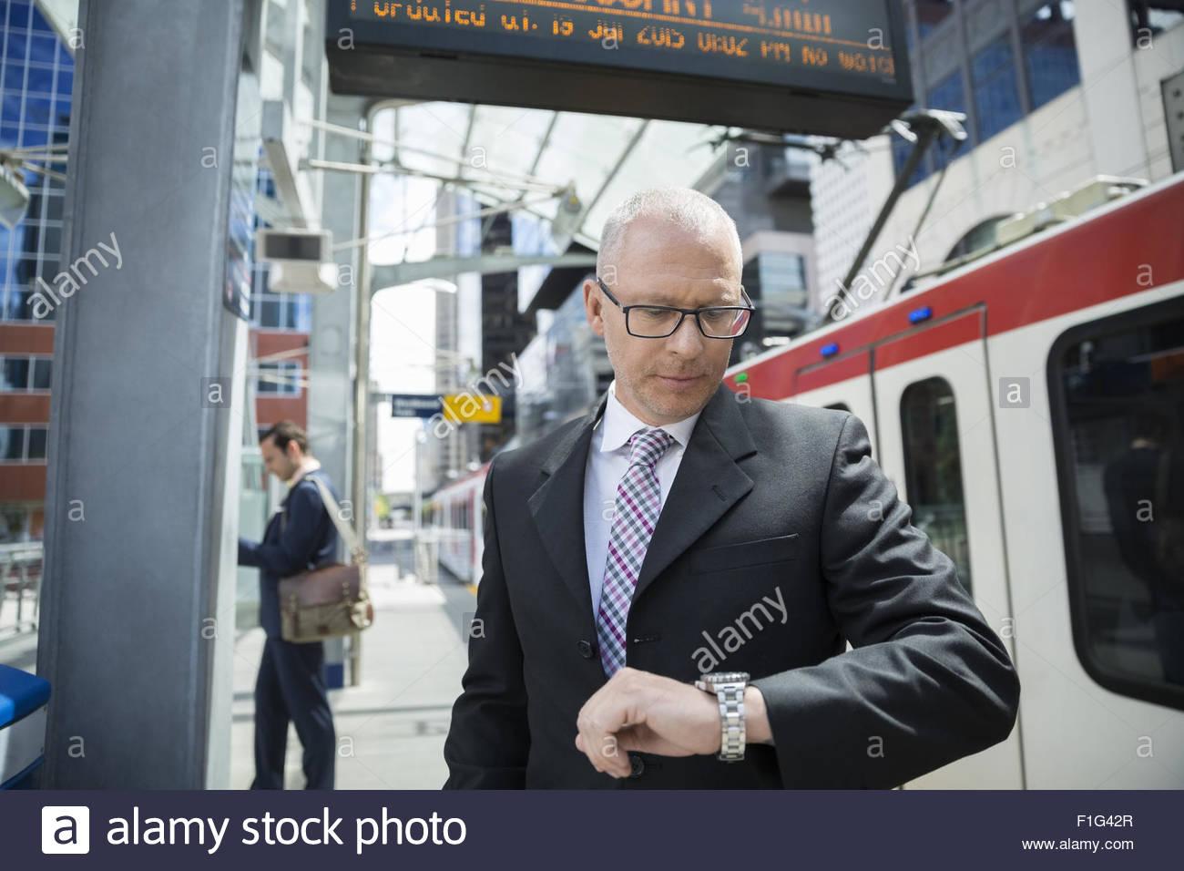 Geschäftsmann, überprüfen der Zeit auf Armbanduhr am Bahnhof Stockbild