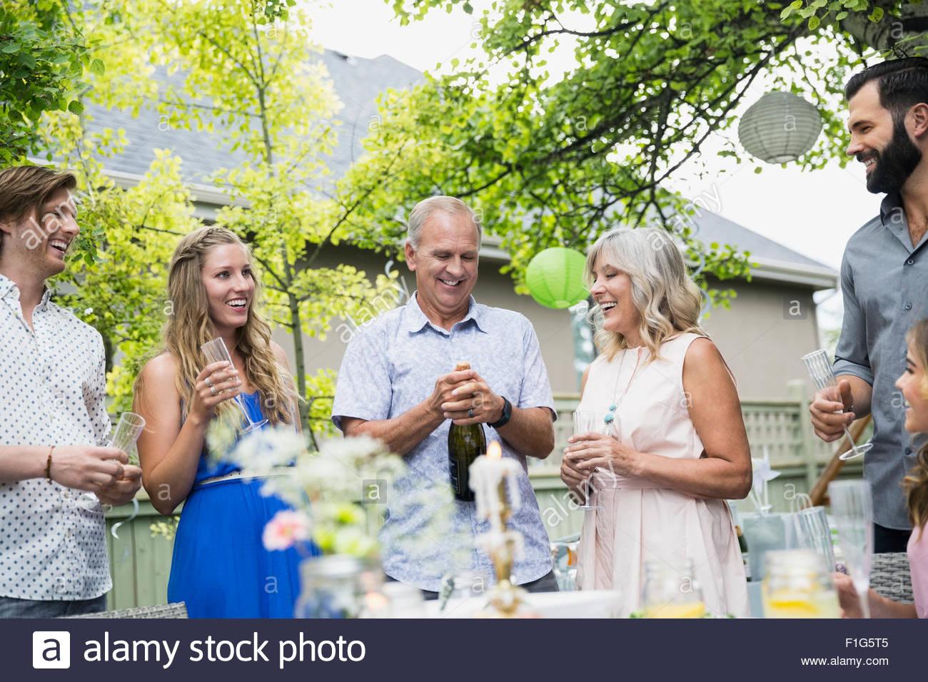 Mann öffnet Sektflasche mittags Gartenparty Stockbild