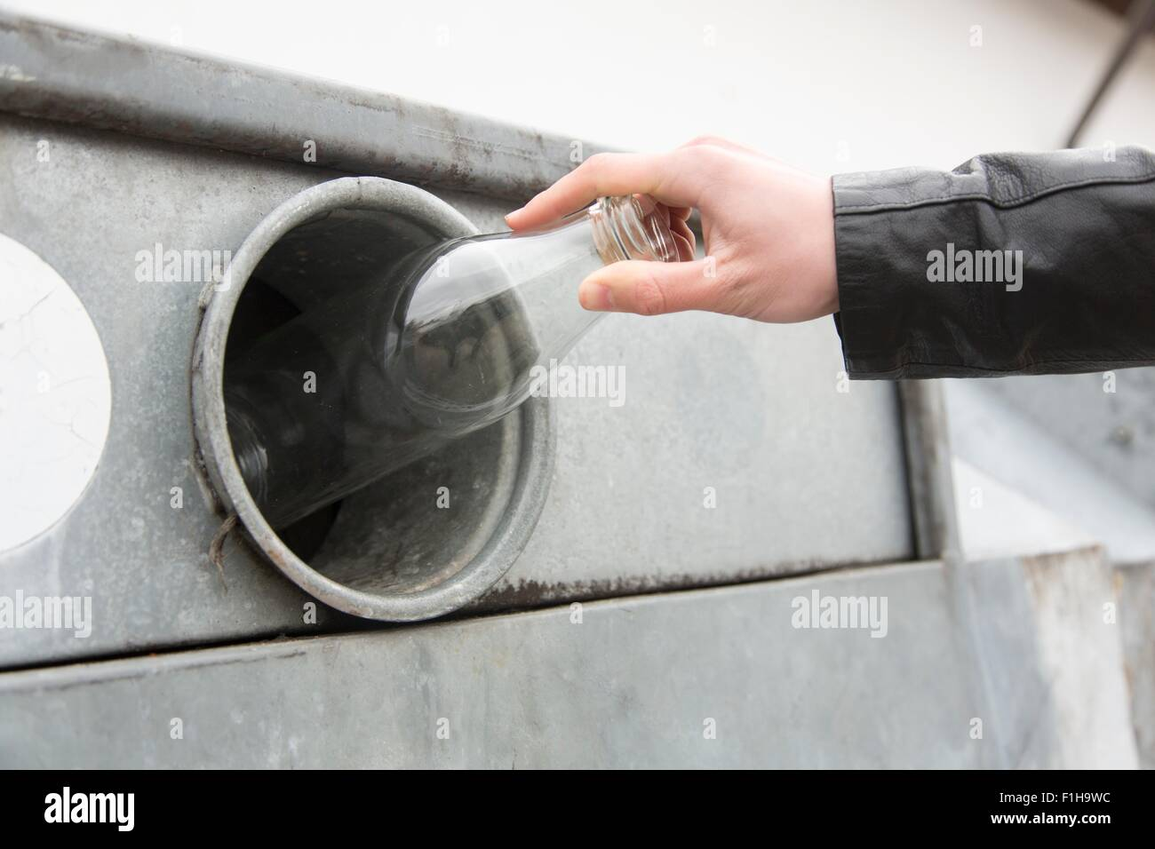 Person recycling Milchflasche in Altglascontainer Stockbild
