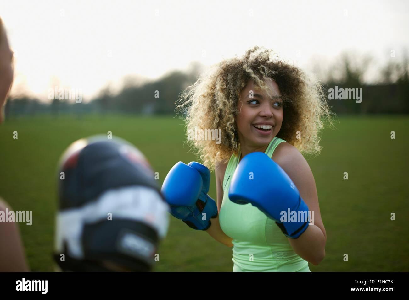 Zwei Frauen mit Boxhandschuhen im Park trainieren Stockbild