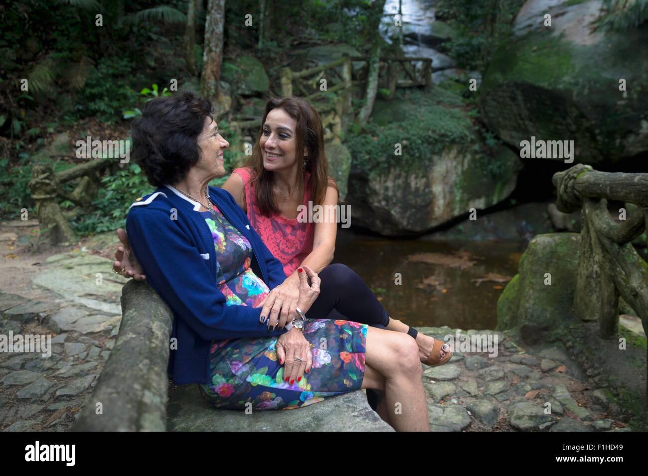 Ältere Frau und Tochter Hand in Hand am Wald river Stockbild