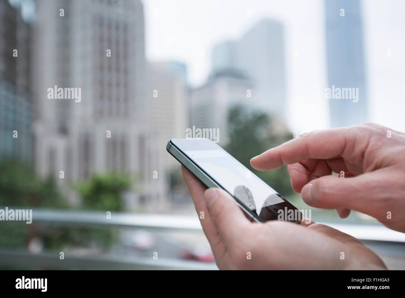 Mann mit Smartphone im Freien, Fokus auf Händen, Hong Kong, China Stockbild
