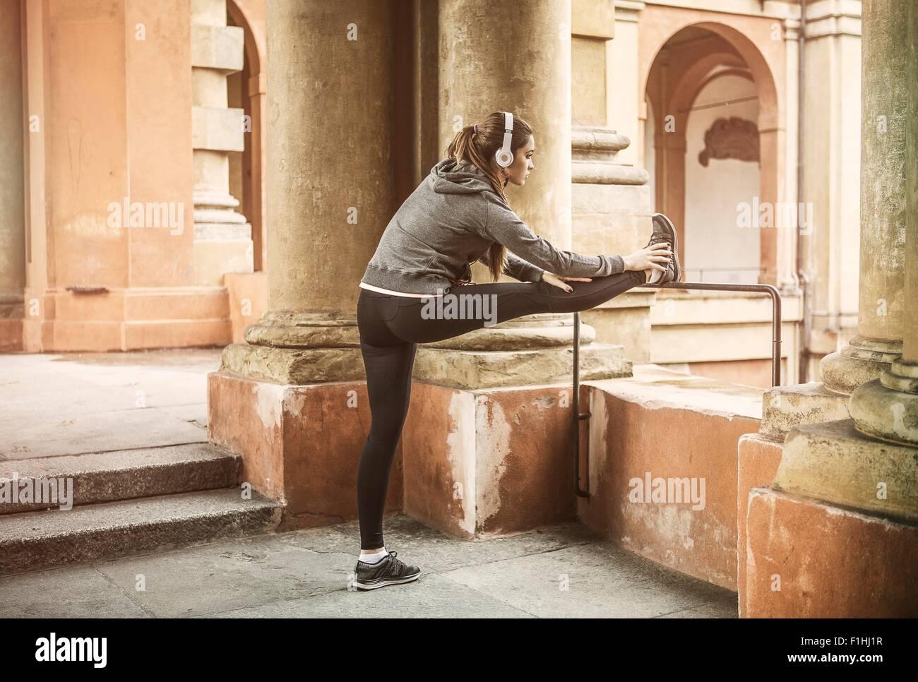Junge Frau trägt Sportkleidung und Kopfhörer, die Beine Stockbild