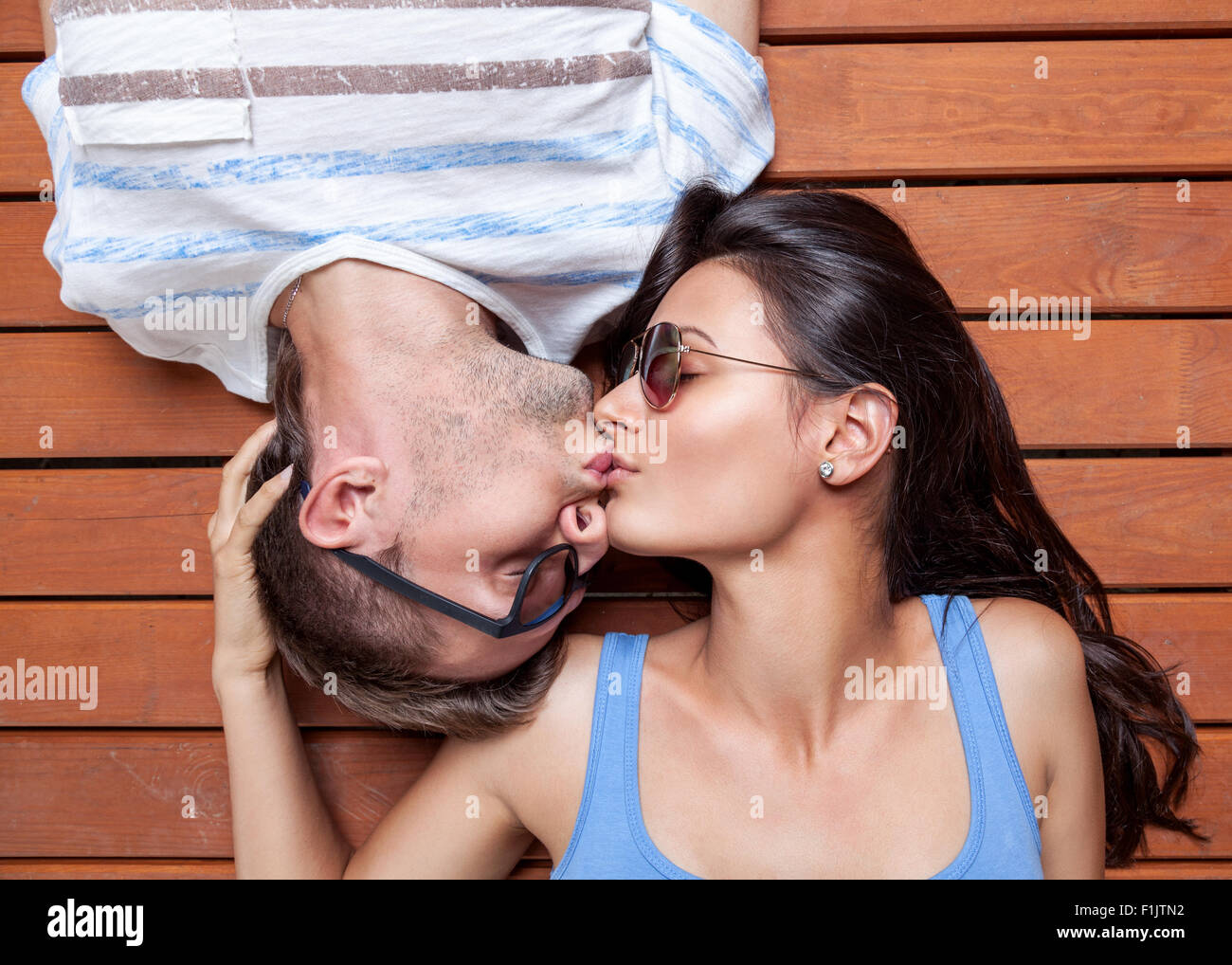 Glückliches junges Paar liegen Kopf an Kopf auf einem Holzfußboden Stockbild
