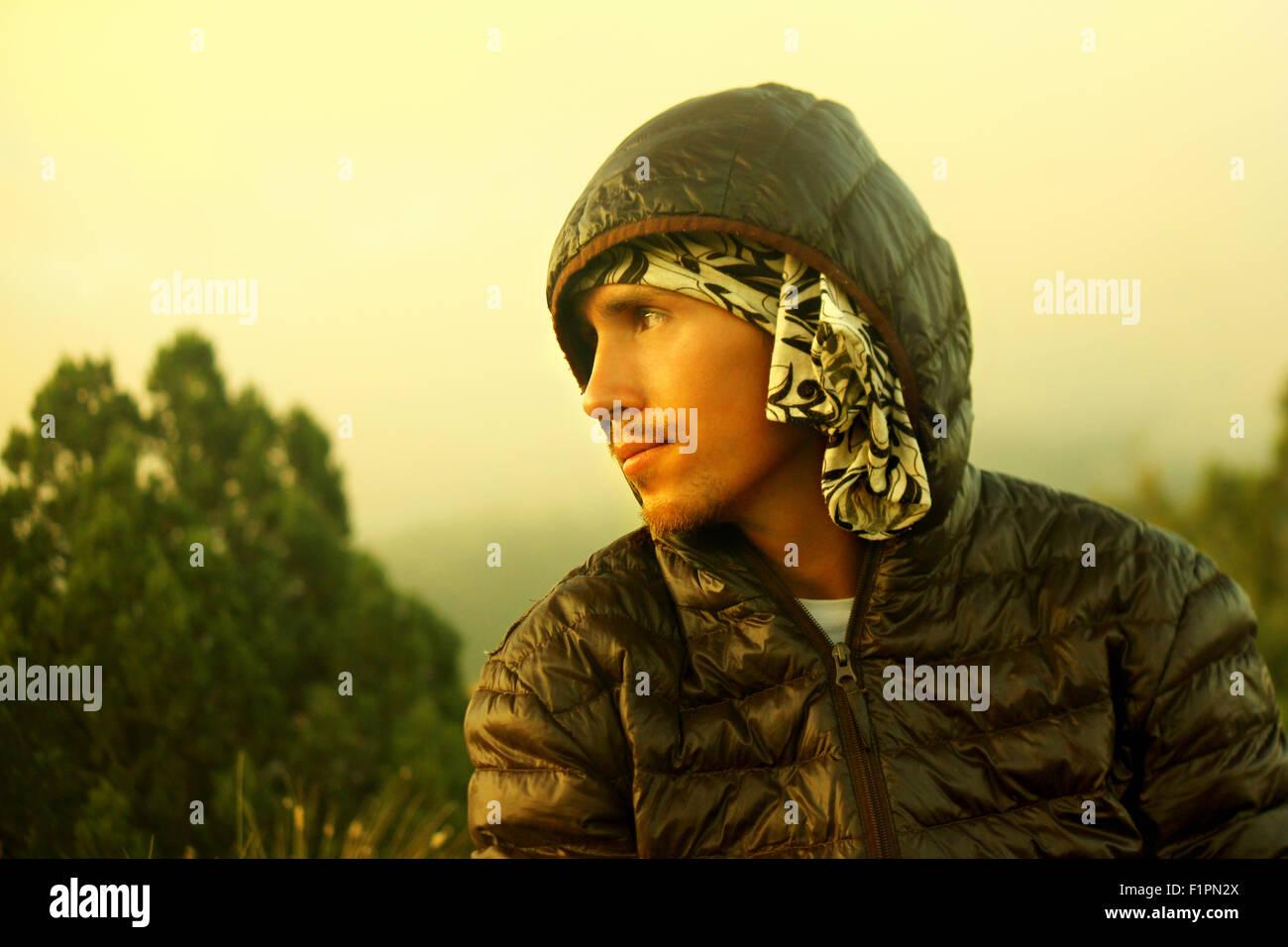 Schönen jungen Mann mit Bart im Herbst dunkle Jacke mit Kapuze hinunter in die wilde Blicke entfernt. Filter Stockbild