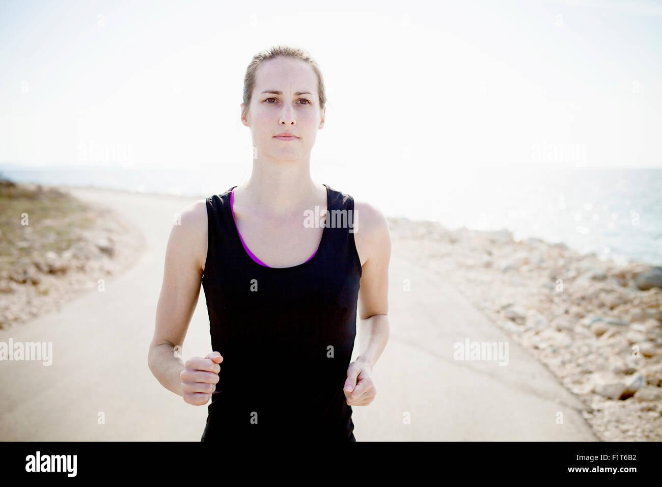 Frau in Sportbekleidung Joggen am Wasser Weg Stockbild