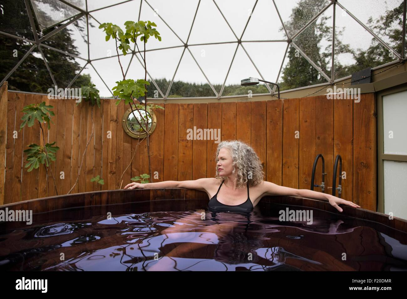 Reife Frau Entspannung im Whirlpool bei Eco retreat Stockbild