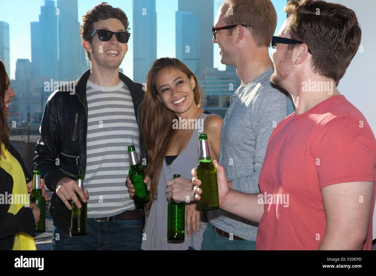 Fünf Erwachsene Freunde trinken Bier an der Bar auf der Dachterrasse mit Skyline von Los Angeles, USA Stockbild