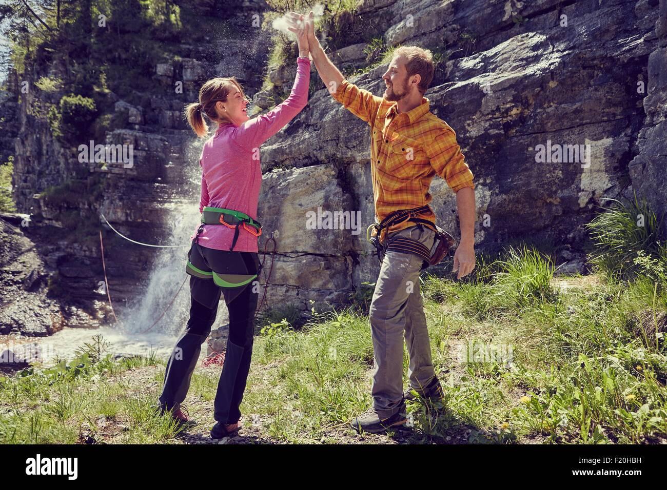 Kletterer geben hohe fünf, Wasserfall im Hintergrund, Ehrwald, Tirol, Österreich Stockbild