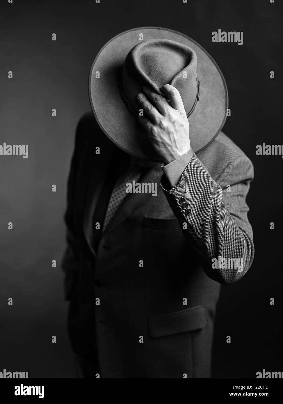 Männchen tragen dunkle Anzüge und er bedeckte Gesicht mit einem Hut, schwarz-weiß-Bild Stockbild