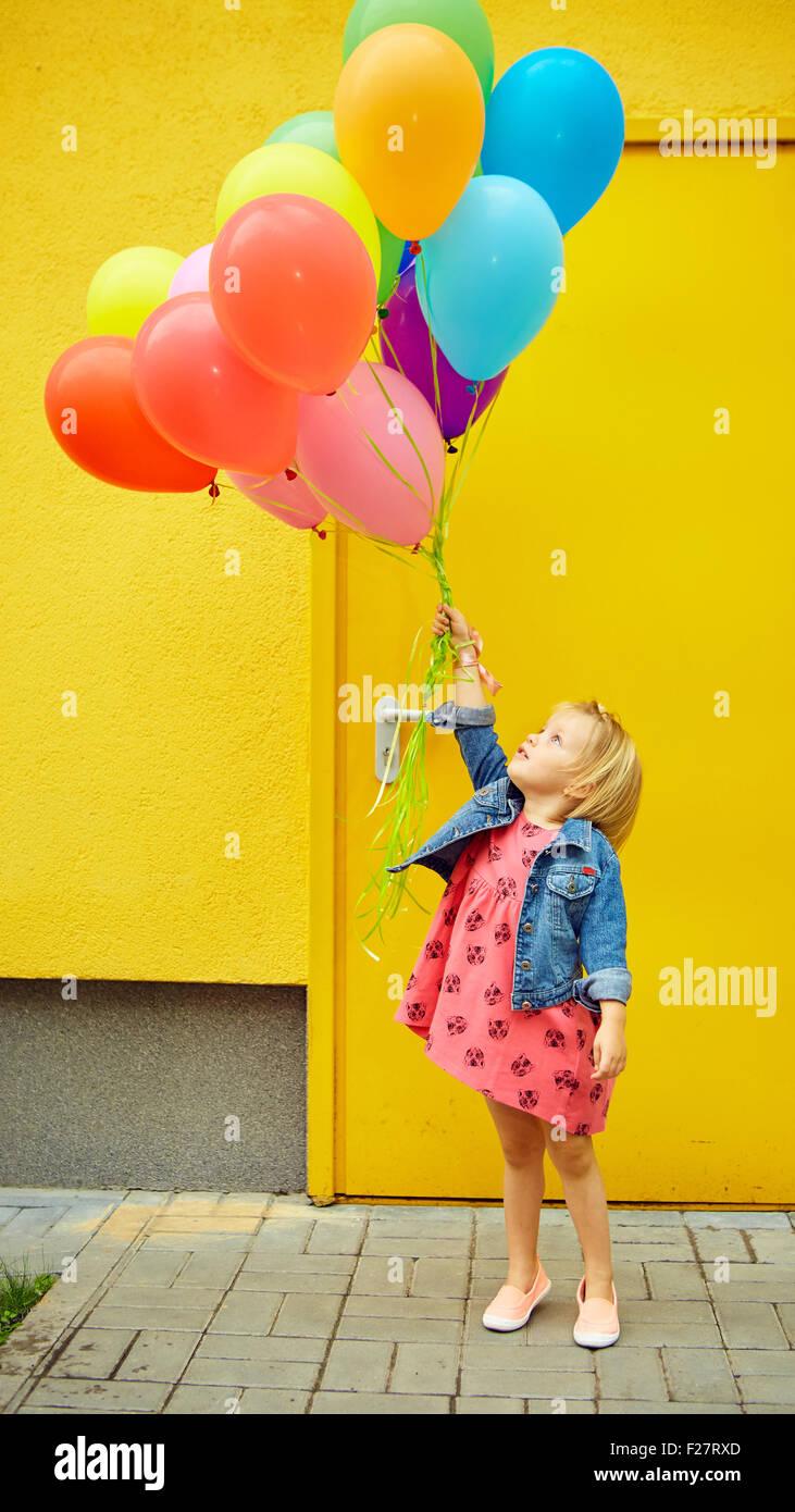 glückliche kleine Mädchen im Freien mit Luftballons Stockbild