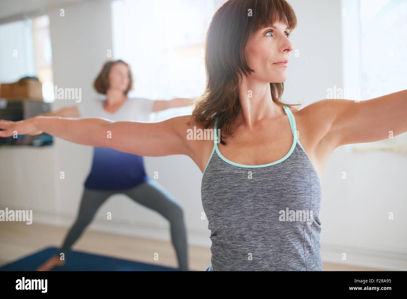 Fitness-Trainer tut der Krieger-Pose während der Yoga-Kurs. Yoga-Lehrerin Durchführung Virabhadrasana Stockbild