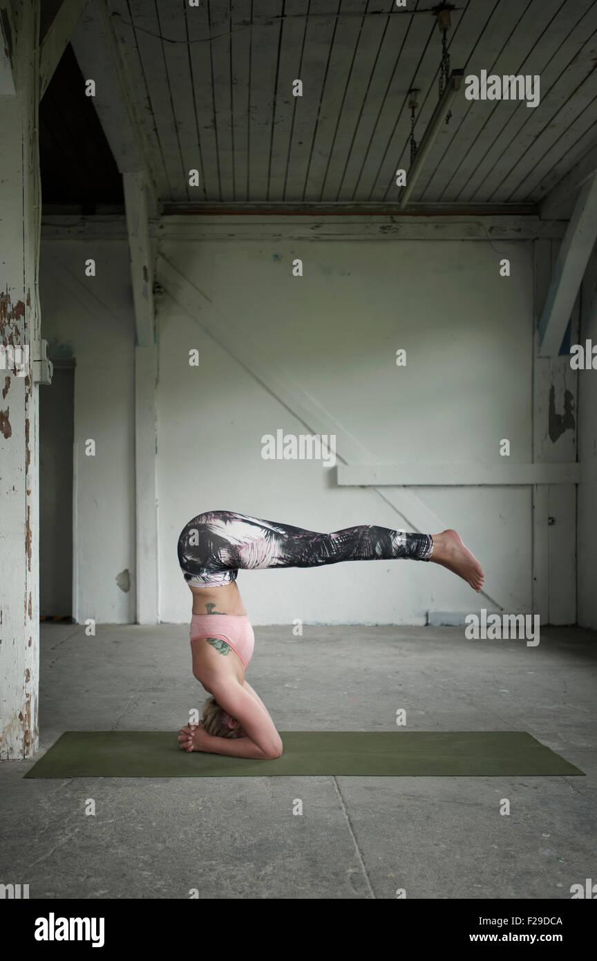 Mitte Erwachsene Frau üben Kopfstand Pose im Yoga-Studio, München, Bayern, Deutschland Stockbild