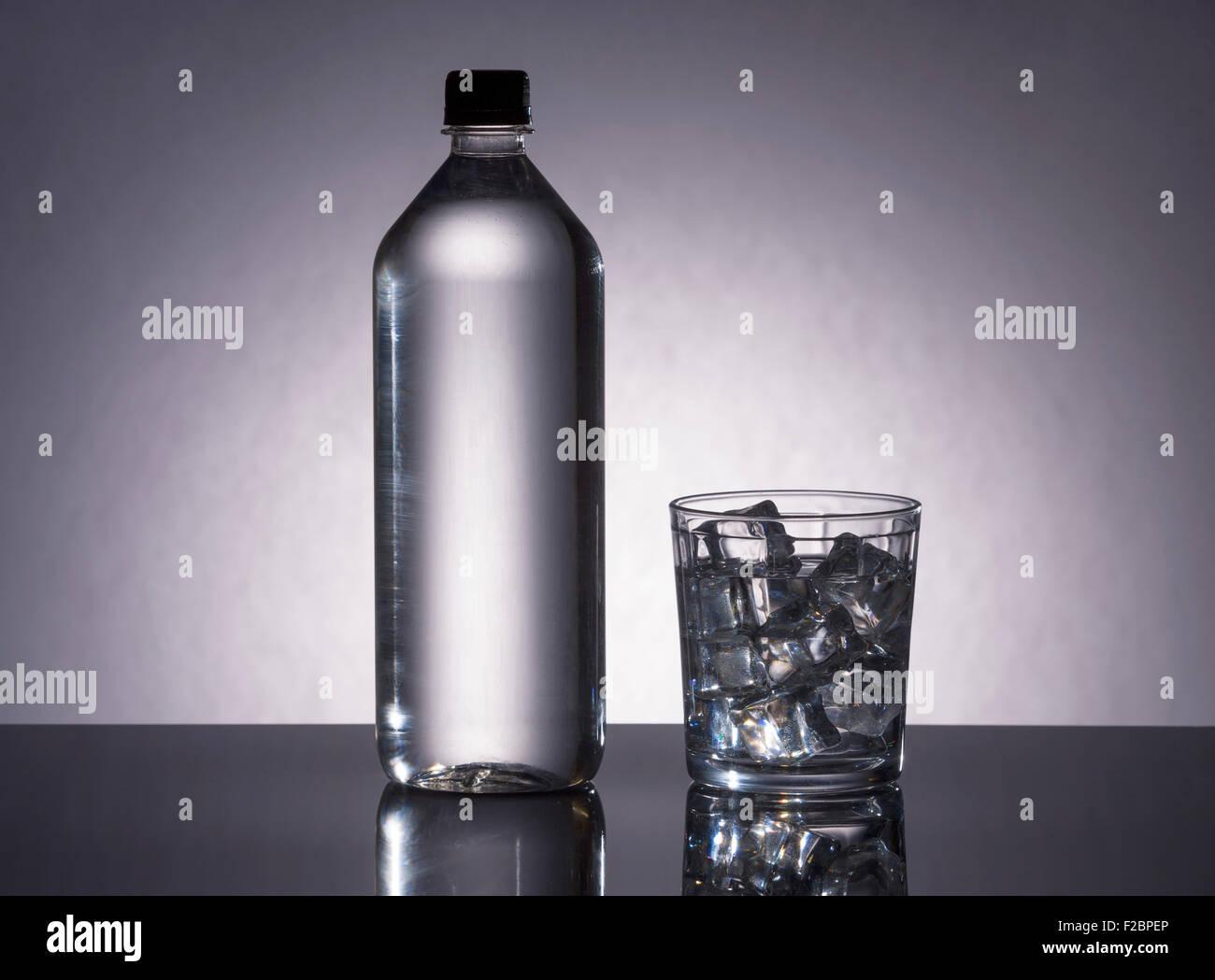 Flasche und Glas mit H2O gefüllt. Stockbild
