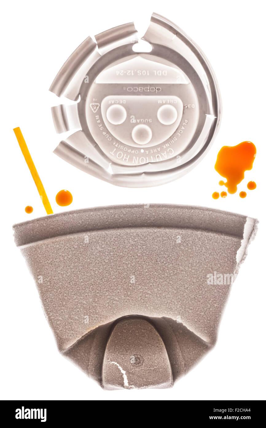 abgeflachte Styropor Kaffeetasse mit Kappe oben und gelbe rühren Stick auf Leuchttisch mit Tropfen Kaffee Stockbild