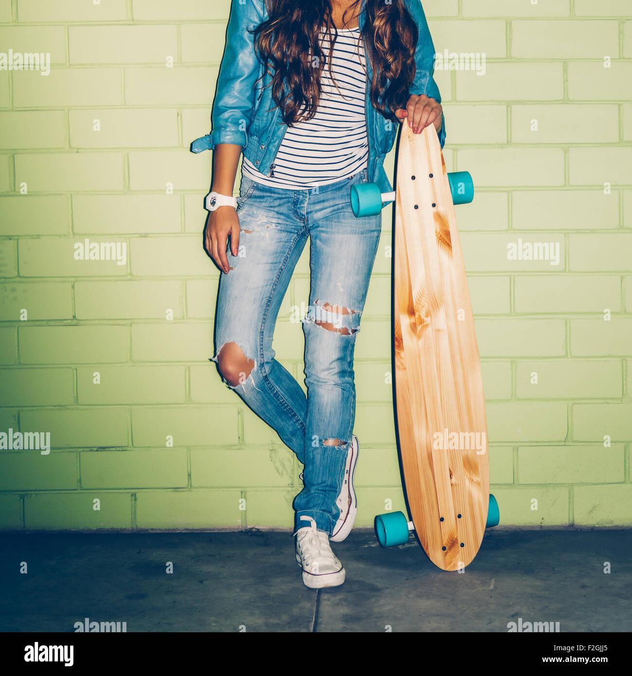 schöne langhaarige Mädchen mit hölzernen Longboard Skateboard Stand in der Nähe der grünen Mauer Stockfoto