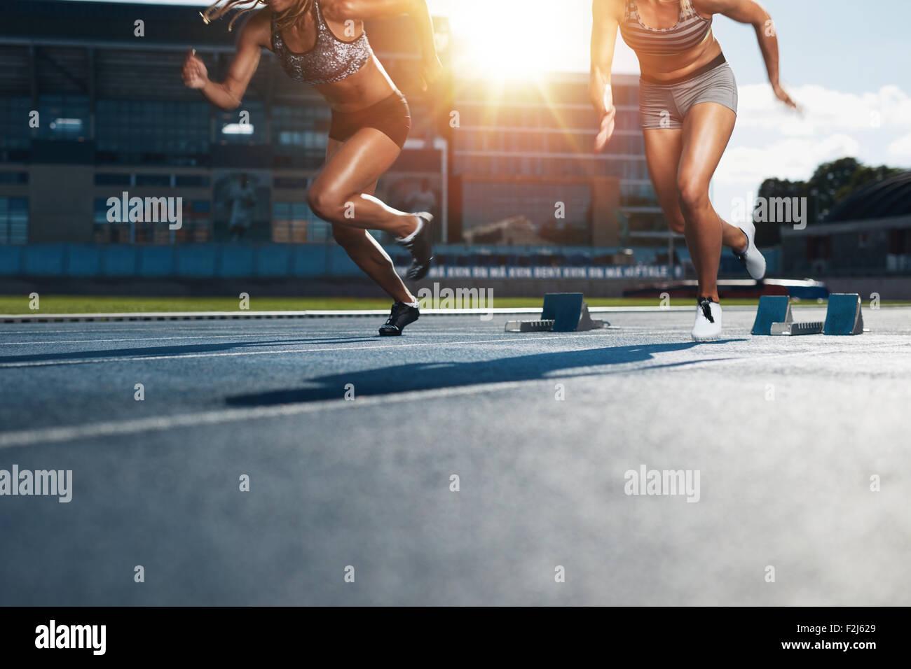 Sprinter beginnt aus den Blöcken auf Leichtathletik-Rennstrecke mit hellem Sonnenlicht. Niedrige Abschnitt Stockbild