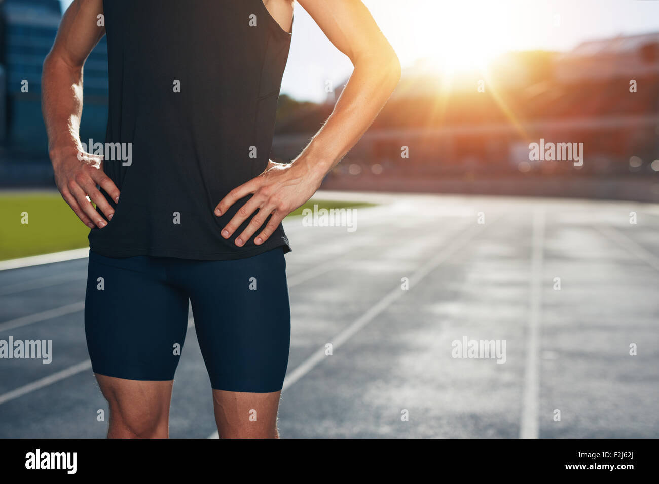 Mittelteil verfolgen Schuss von männlichen Athleten stehen auf Rennen mit seinen Händen auf den Hüften Stockbild