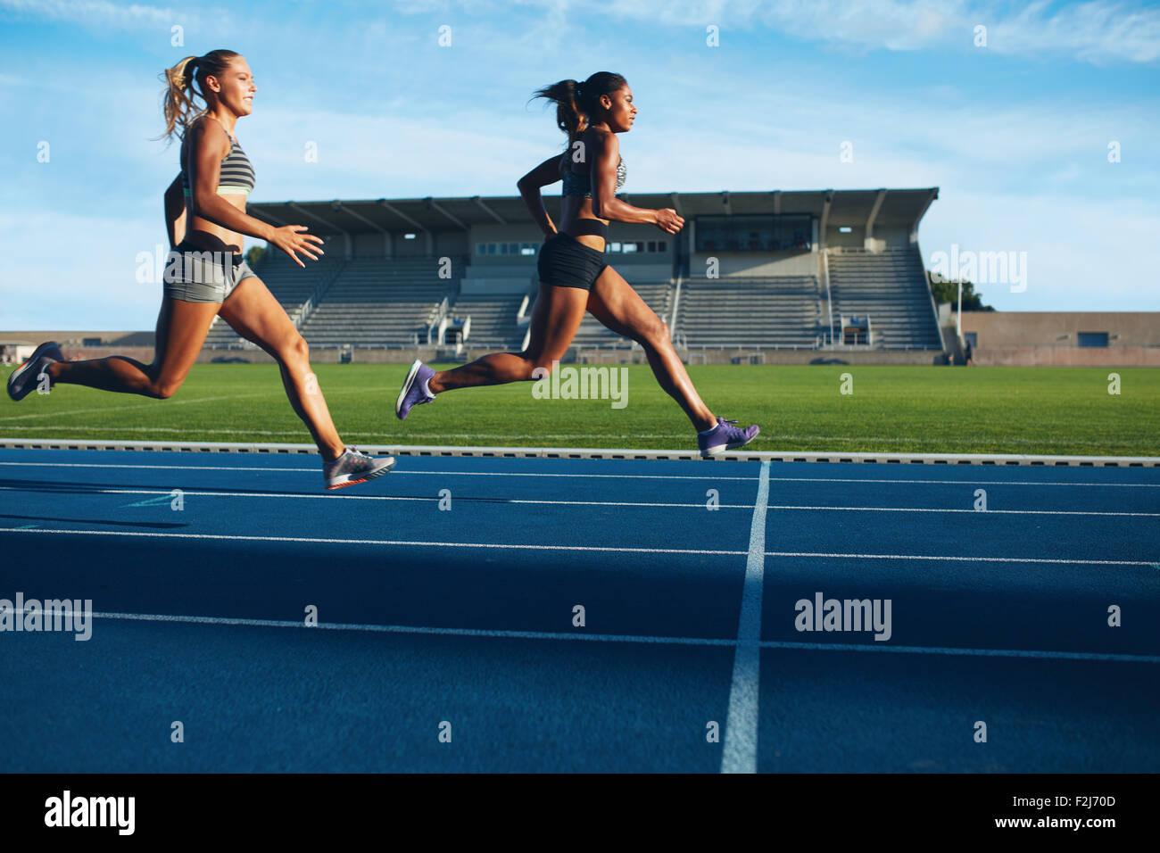 Athleten erreicht Ziellinie auf Rennstrecke während der Trainingseinheit. Junge Weibchen konkurrieren in einem Stockbild