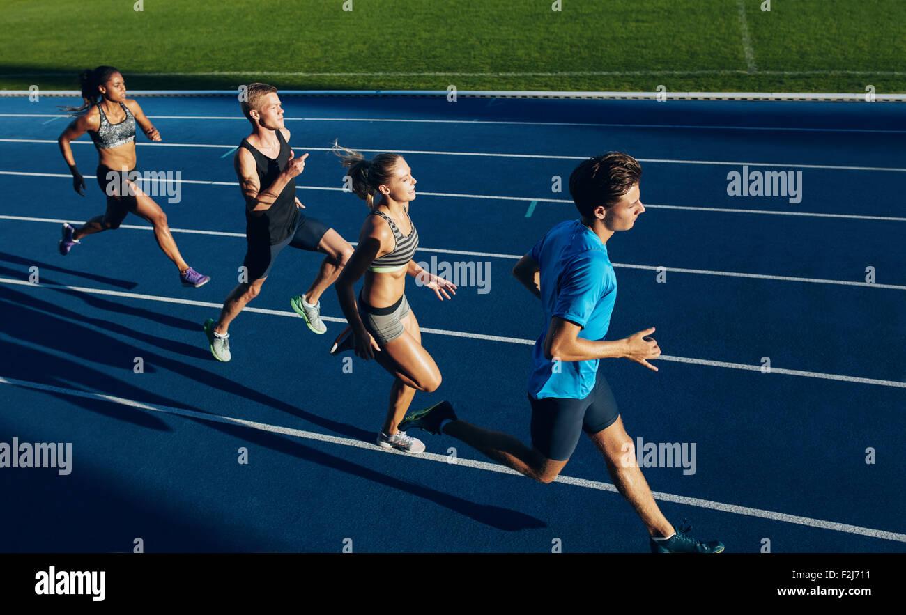 Gruppe von Rassen Athleten üben auf Rennstrecke ausgeführt. Athletinnen und Athleten während der Stockbild