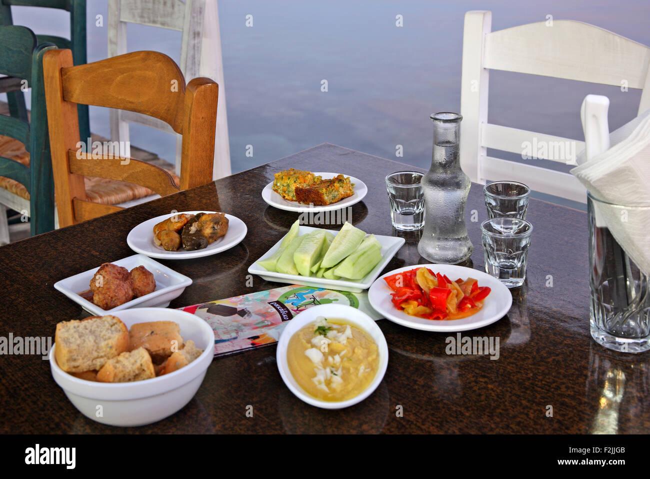Tabelle mit traditionellen kretischen Gerichten und Raki, das traditionelle kretische trinken in einer Taverne in Stockbild